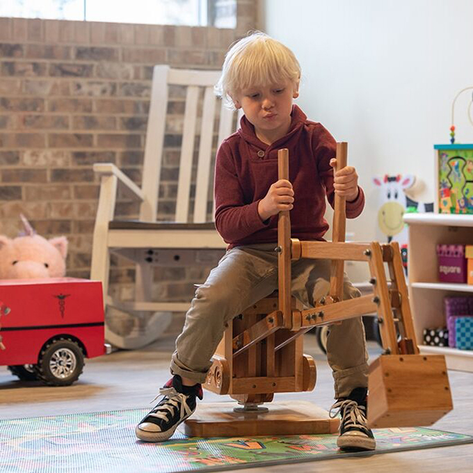 Young boy playing on a wooden toy